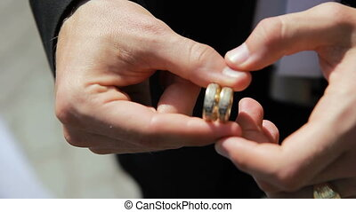 Man holding two wedding rings in his hands and turns them...
