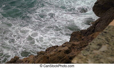 The sea surf in the bay on a cloudy day. A small storm. Polenca and Port