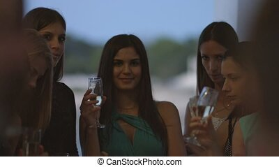 Group of beautiful women with glasses of champagne in the...