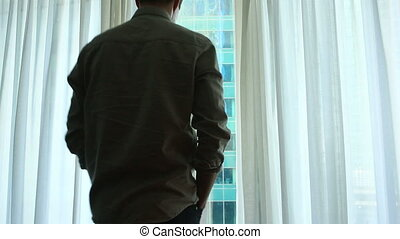 A man stands by the window with curtains in a hotel room,...