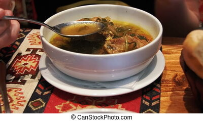 Woman Eating Mutton Soup in the Restaurant. Soup of Piti,...