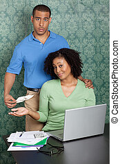 Young man holding out empty pocket in front of woman while...