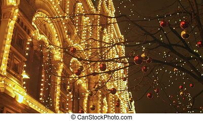 Urban street trees are decorated in New Year's and Christmas toys on the background of the building with evening illumination.
