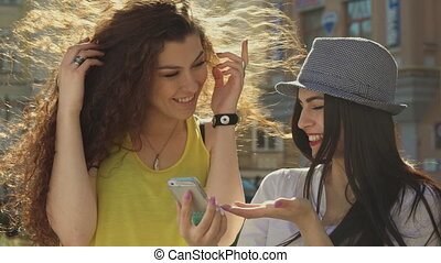 Two girls discuss something on smartphone