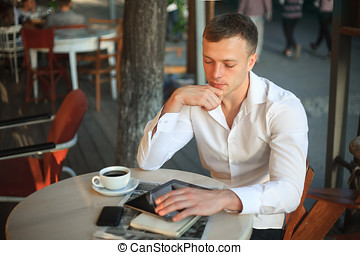 Young man using digital tablet computer in street cafe.