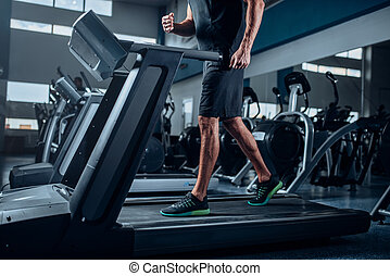 Male person workout on running exercise machine. Active...