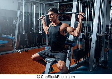 Tanned athlete workout on exercise machine in gym. Active...