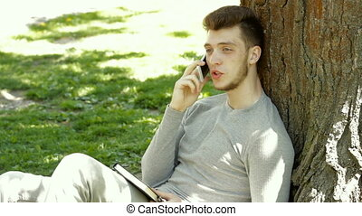 guy in the park under a tree talking on mobile phone - a...