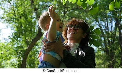 The grandmother of the child is resting, playing in the Park. The outdoors. Family holiday in the park