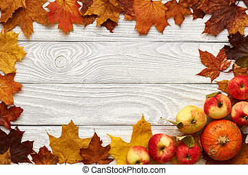 Autumn leaves, apples and pumpkins over wooden background -...