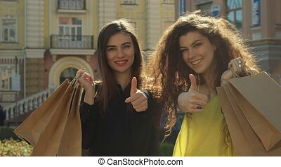 Female friends approve their shopping in the city