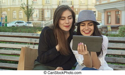 Female friends watch something on the tablet outdoors