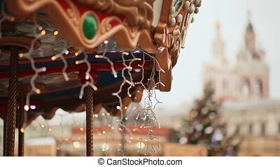 Christmas carousel rotating with children, decorated with illumination. Moscow. Area of the city. New Year theme.