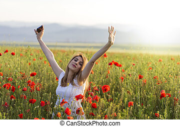 Girl standing in a poppy field with hands up with phone