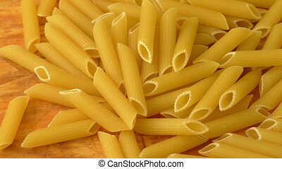 Raw pasta on wooden chopping board