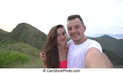 Young couple taking selfie, laughing and go round in the mountains with beautiful aerial city view at sunset, enjoy the nature and carefree life