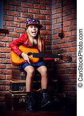 pop music star - Modern child girl playing guitar and...
