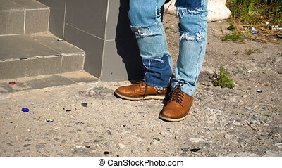 male feet in brown shoes and blue jeans - close up of male...