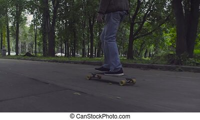 Young man riding on longboard on the road.