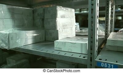 Close up hand of Man takes box from shelf inside warehouse....