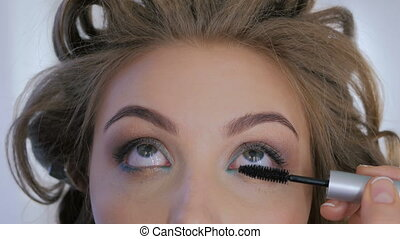 Professional make-up artist applying mascara on eyelashes of...