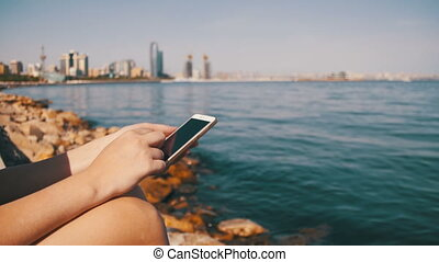 Young Woman using Mobile Phone Sitting on Embankment near...