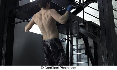 An athlete in training does pull-ups in a boxing gym. Tired...