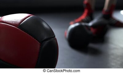 Boxing gloves and med ball laying on the floor near in ring