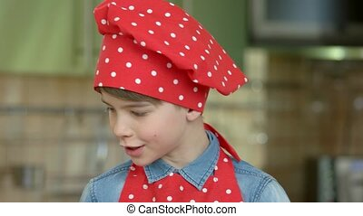 Caucasian boy wearing chef hat. Kid on blurred background.