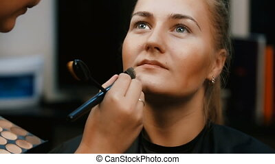 Make up artist doing professional make up of young woman. -...
