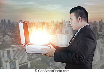 asian business man open business briefcase with surprising...