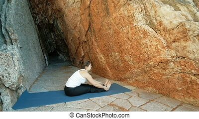 Sport woman doing stretching exercises sitting on mat...
