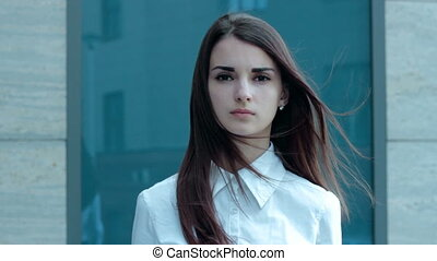 a serious young woman shows no gesture on the street