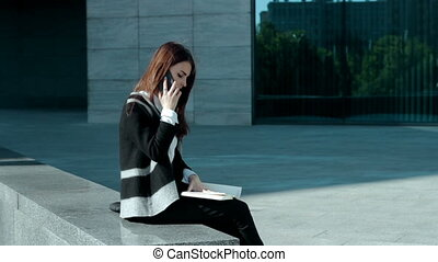 woman talks by mobile phone on the street - business woman...