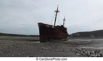 Rusty wreckage shipwreck on deserted shore beneaped dried-up...