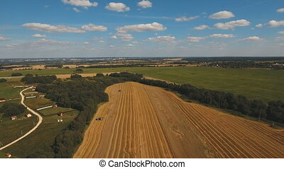 Aerial view combine harvesting a field of wheat. - Two...