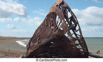 Rusty wreckage shipwreck of cargo ship on beach ocean in San...