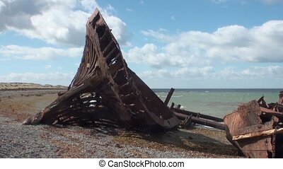 Rusty wreckage shipwreck of cargo ship on beach ocean in San...