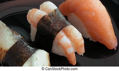 Sushi on black plate spinning in a circle