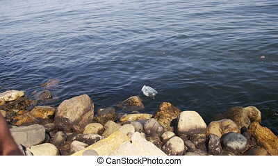 Garbage Floats in the Caspian Sea near the Stones on the Embankment of Baku