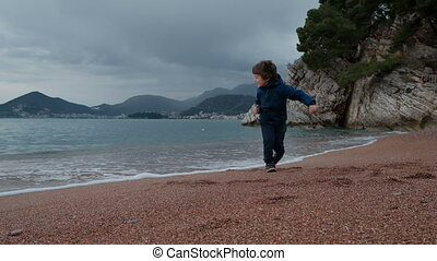 Little boy plays with waves on seashore outdoors.