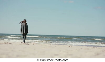 A young dark-haired pregnant woman is walking barefoot on a...