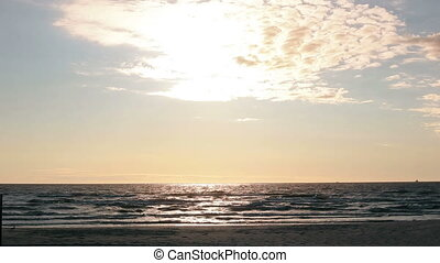 Gentle sun rays light up the surface of the waves coming to...