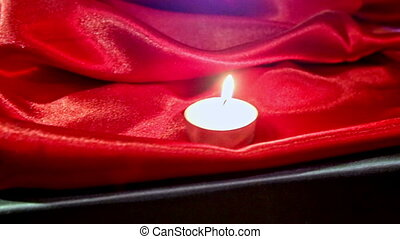 Macro Small Lit Candle on Red Silk Fabric at Bright Light -...