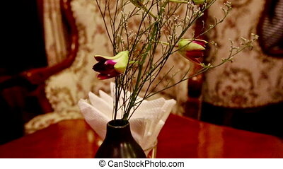 Closeup Vase with Flowers on Table by Chairs in Restaurant