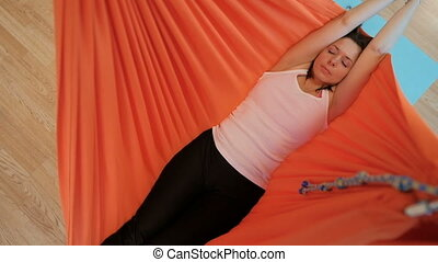 Young woman meditating lying down in hammock indoors....