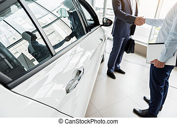 Business deal concerning purchase of new car - Focus on door...