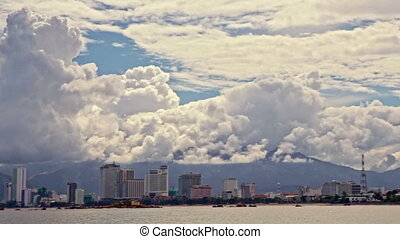 View of Distant Resort City across Sea Bay Cloudy Sky -...