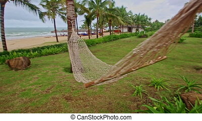 Net Hammock across Palm Alley by Sand Ocean Beach - closeup...