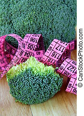 Diet concept broccoli with a pink measuring tape